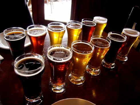 A selection of light and dark beers in glasses on a wooden table