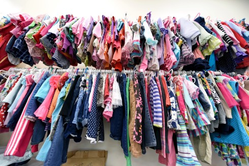 Two racks of multicolored second-hand children's clothes