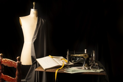 A dressmaker's dummy, pattern book, and old sewing machine.