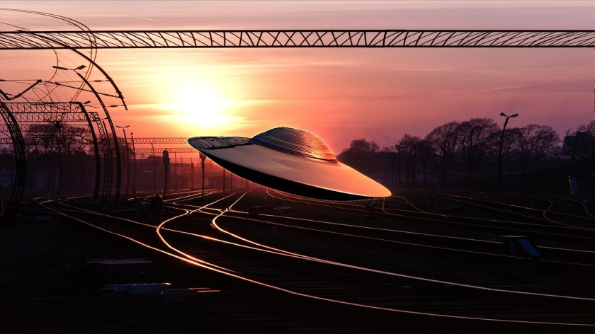 a spaceship flying low over railroad tracks during a sunset