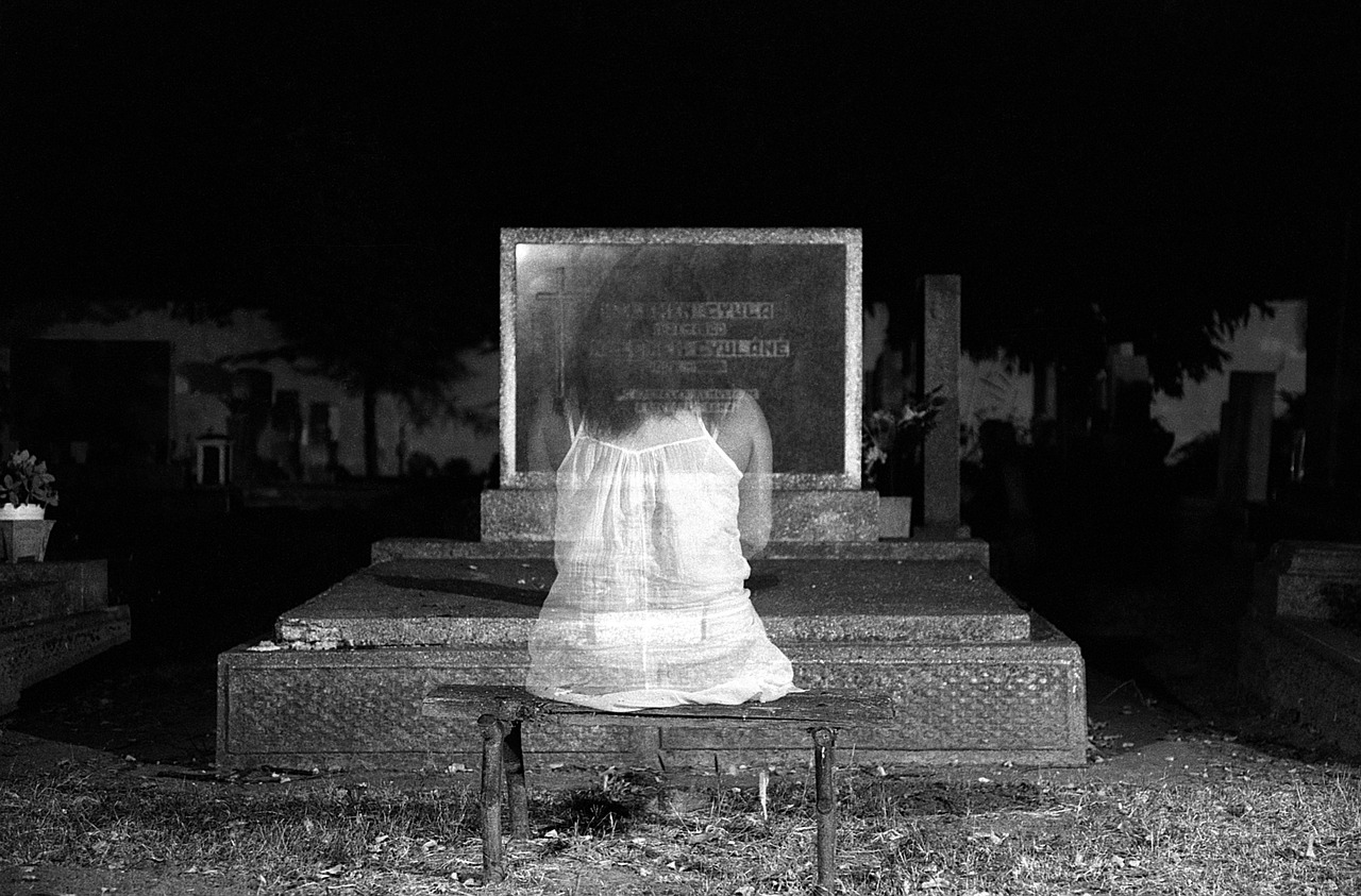 transparent image of a young woman sitting in front of a gravestone