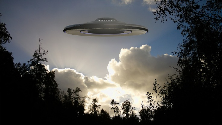 a spaceship in cloudy skies over a forest during daytime
