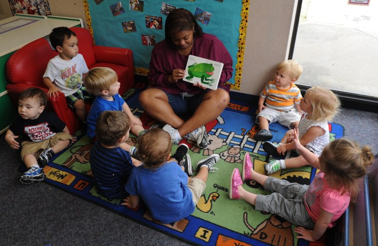 a woman reads a picture book to small children
