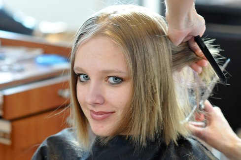 a lady getting her hair cut