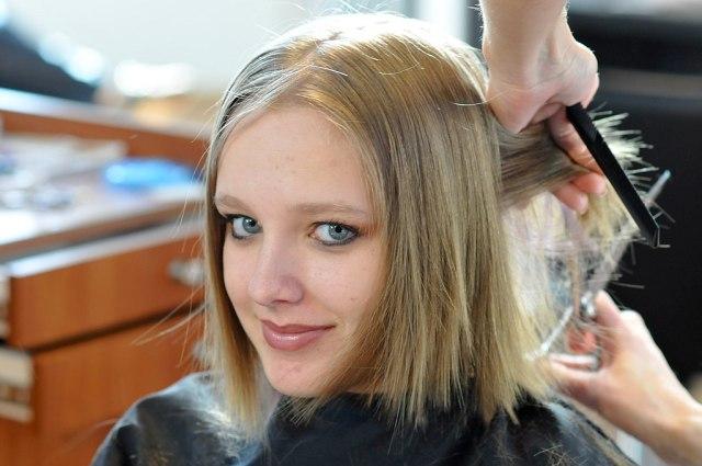 a lady getting her hair cut