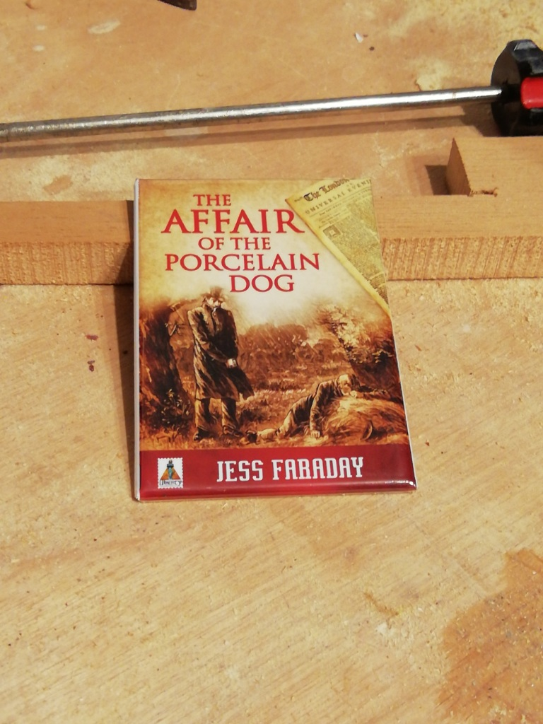 A refrigerator magnet with the cover of The Affair of the Porcelain Dog by Jess Faraday.