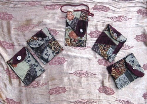 Five small crazy-quilted wallets.
