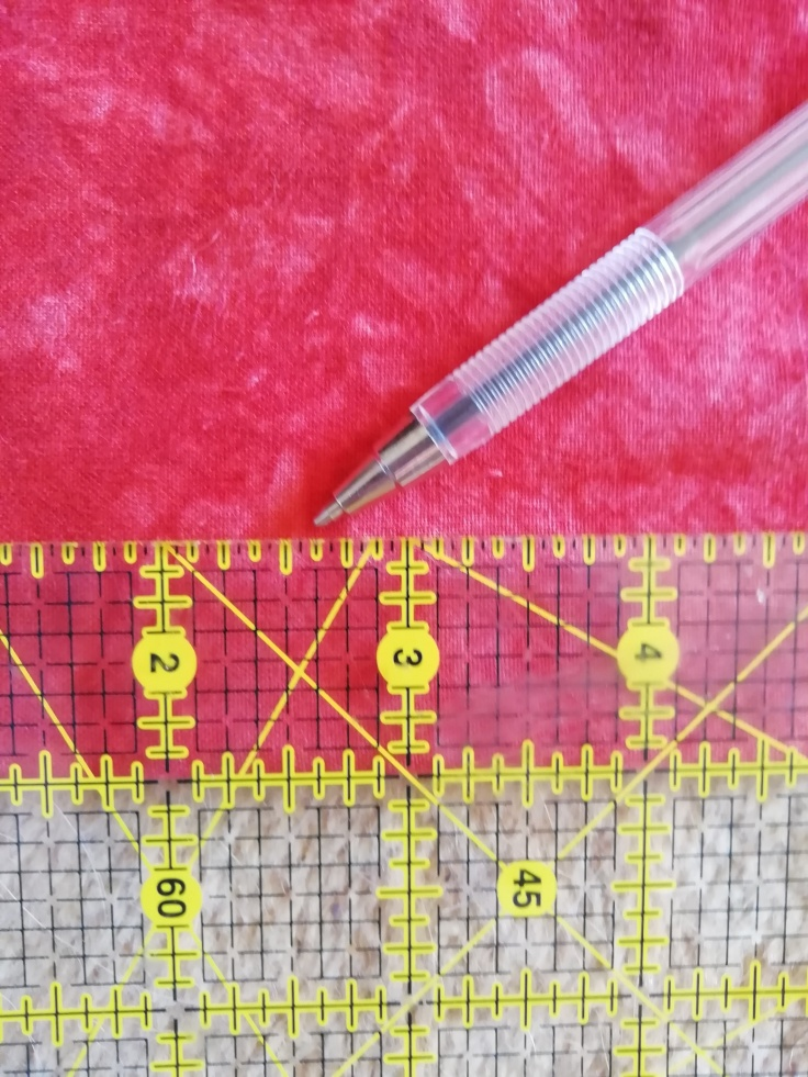 A ruler measures the cut line one inch below the fold.